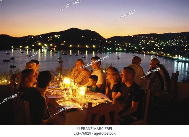 People having dinner in Restaurant Kau-Kan at sunset, Zihuatanejo, Guerrero, Mexico, America