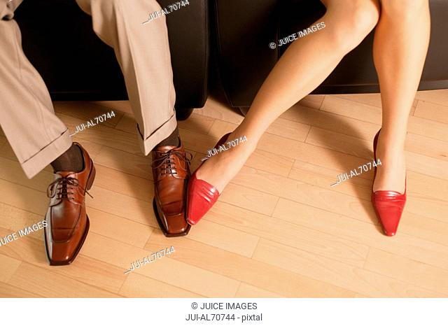 Overview of businessman and woman playing with their feet