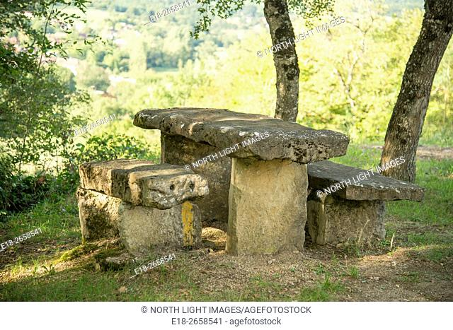 France, Midi-Pyrénées. A picnic table made of solid stone. In the shade of tall trees in the Dordogne Valley