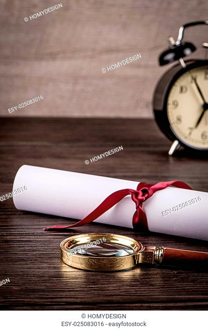 Wrapped paper sheets and magnifying glass on Old Wooden table