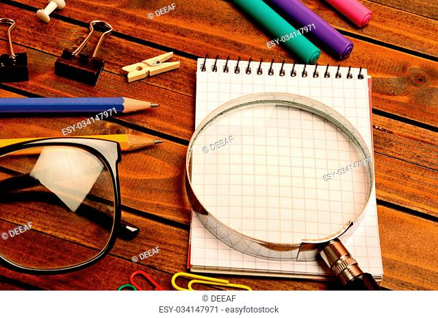 Magnifying glass with notebook on wooden table