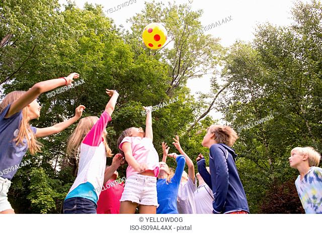 Children playing ball game in garden