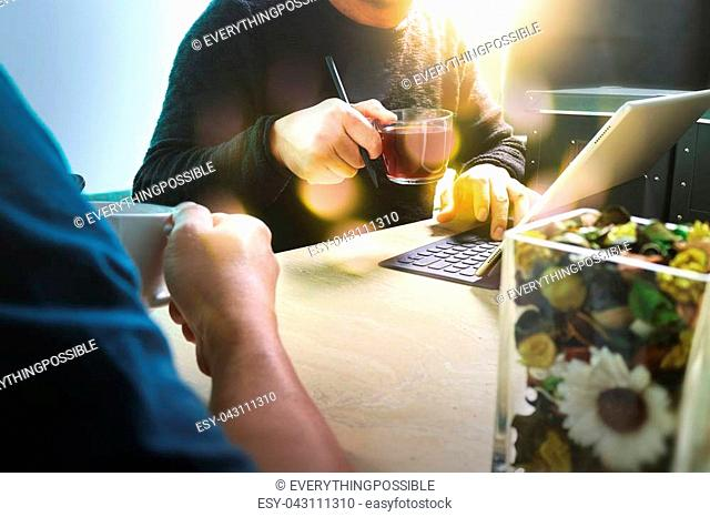 Office coffee break with two designer colleagues sitting chatting over cups of coffee,flower vase,digital tablet docking smart keyboard on marble desk