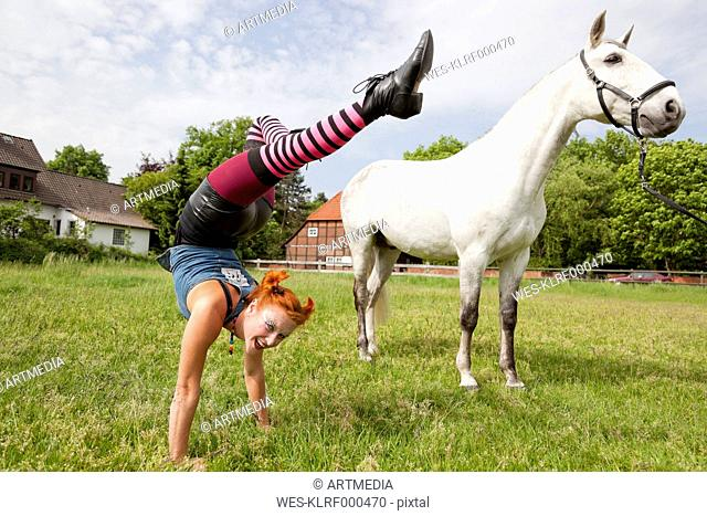 Young woman doing handstand on meadow, grey horse