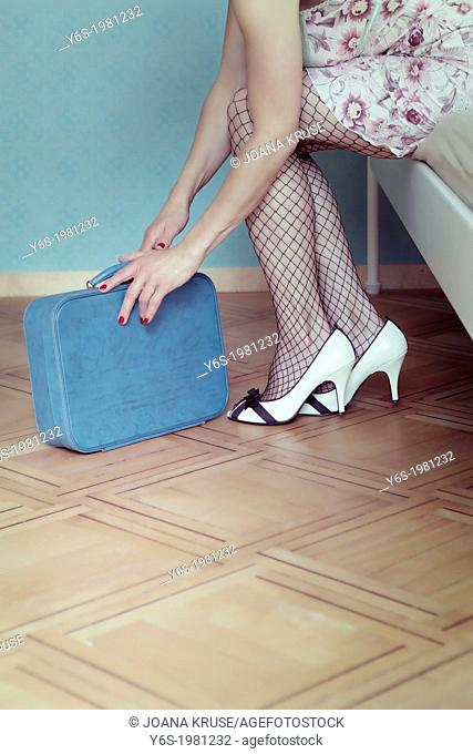 a woman in a negligee is sitting on a bed with a suitcase