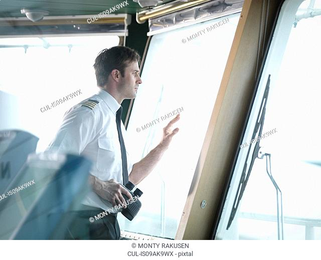 Captain looking out of window on ship's bridge