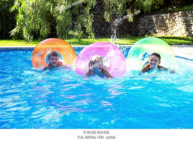 Three children racing on inflatable rings in garden swimming pool