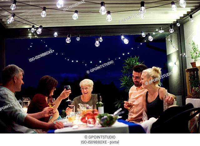 Group of people sitting at table, enjoying meal