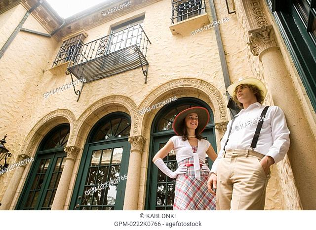 Fashionable young couple in hats standing outside of building, low angle view