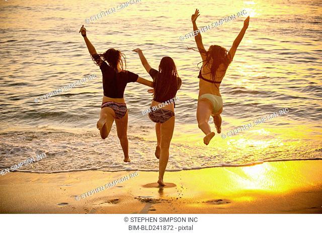 Teenage girls running into ocean at sunset