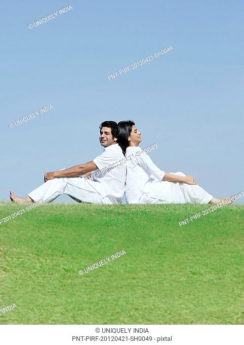 Couple sitting back to back in a park and listening to music, Japanese Park, Rohini, Delhi, India