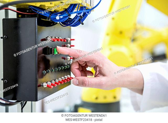 Close-up of woman switching on switch in factory
