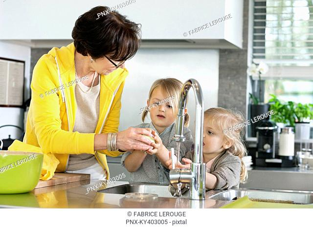 Elderly woman with her granddaughters washing in a kitchen