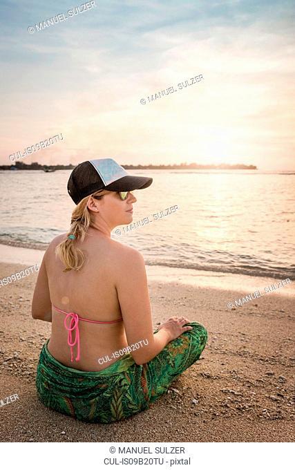 Young woman sitting cross legged on beach, Gili Meno, Lombok, Indonesia