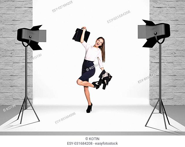 Business woman in photo studio room with white cloth and spotlights