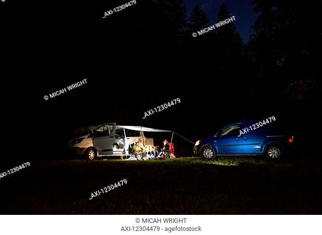 Couples camping together outside their camper vans at nighttime; Bled, Slovania