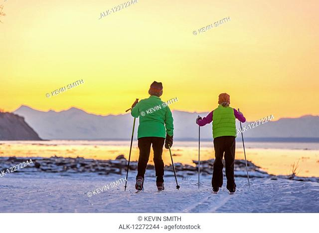 Two back lit people cross country skiing on the Tony Knowles Coastal Trail at sunset, Southcentral Alaska