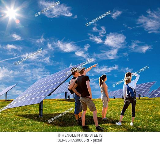 People standing in field by solar panels