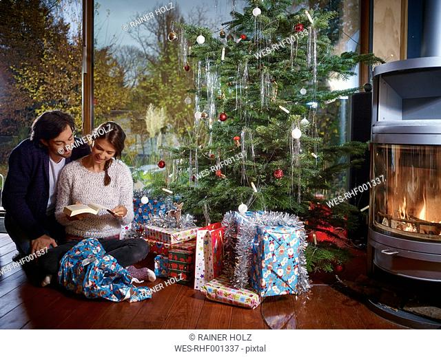 Couple reading book under Christmas tree