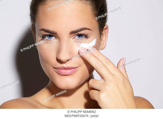 Portrait of beautiful young woman applying skin cream