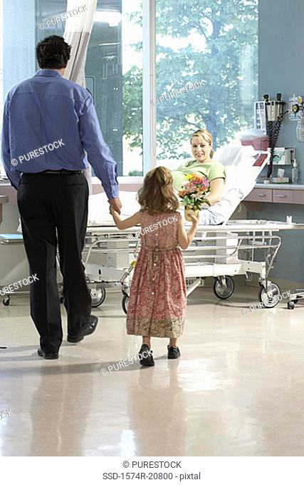 Rear view of a girl holding her father's hand and walking towards her mother