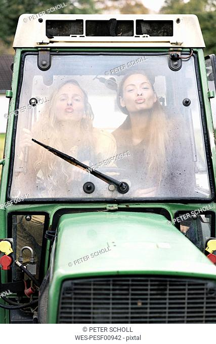 Two woman in tractor, pouting