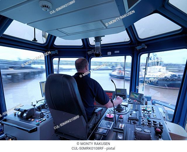 Worker driving tugboat in wheelhouse