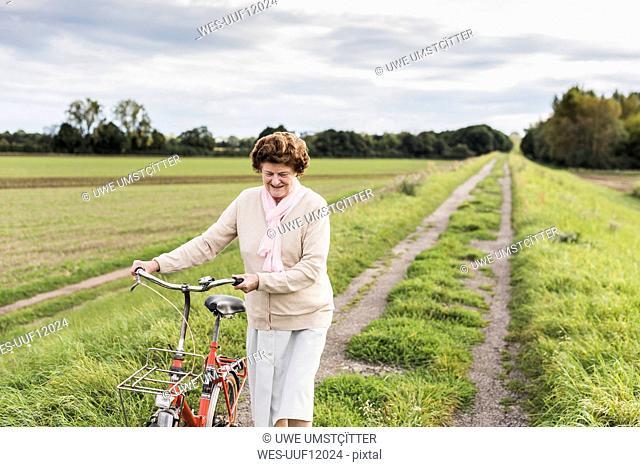 Senior woman pushing bicycle in rural landscape