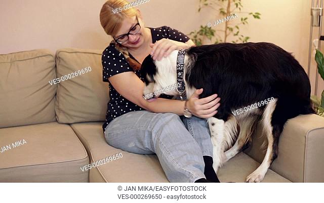 Happy woman relaxing and playing with a dog on the sofa at home