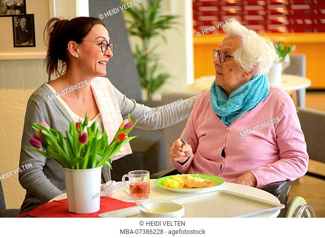 Old woman eating in retirement home with nurse, portrait