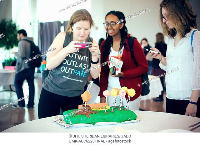 """Undergraduate students taking pictures of a cake decorated for """"""""The Lorax"""""""" at the Edible Book Festival at Johns Hopkins University, Baltimore, Maryland"""