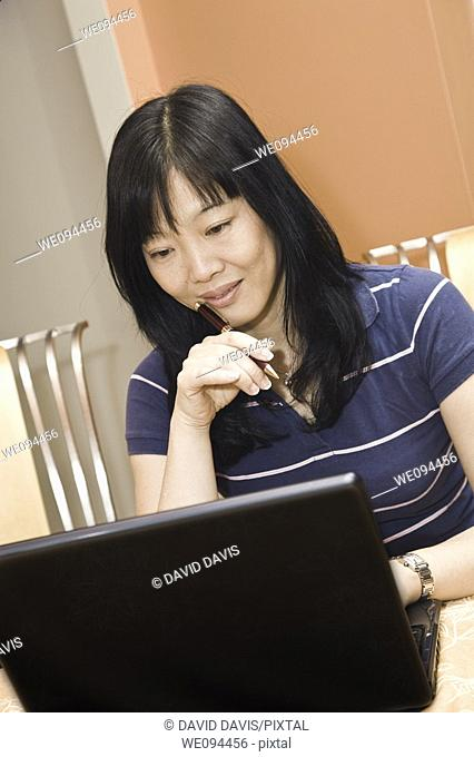 Beautiful Asian woman working on a laptop computer