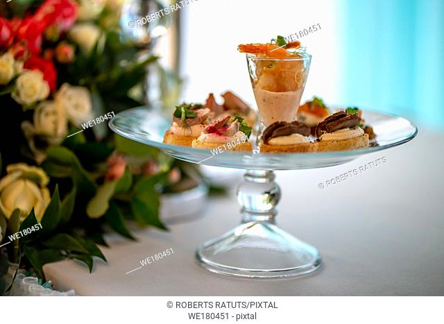 Glass of shrimp salad and sandwiches on the wedding table. Shrimp salad and sandwiches on festive plate