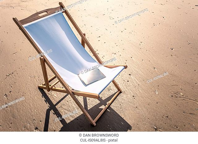 Deck chair on beach with electronic book on seat
