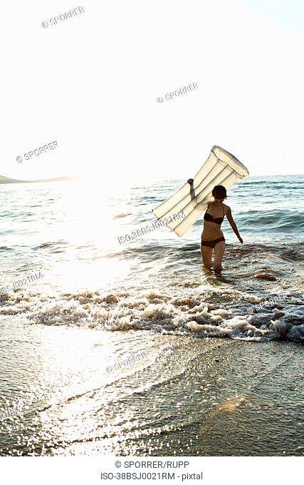 Woman with inflatable mattress on beach