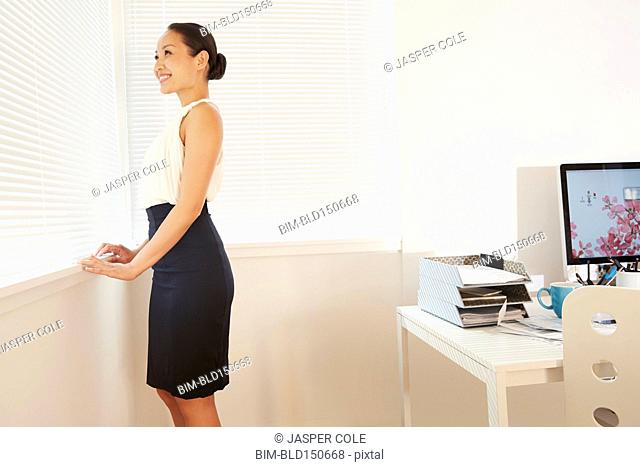 Chinese businesswoman looking out office window