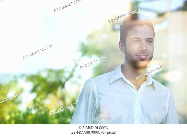 Businessman looking out of window from office