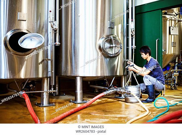 Man working in a brewery, kneeling beside a metal beer tank
