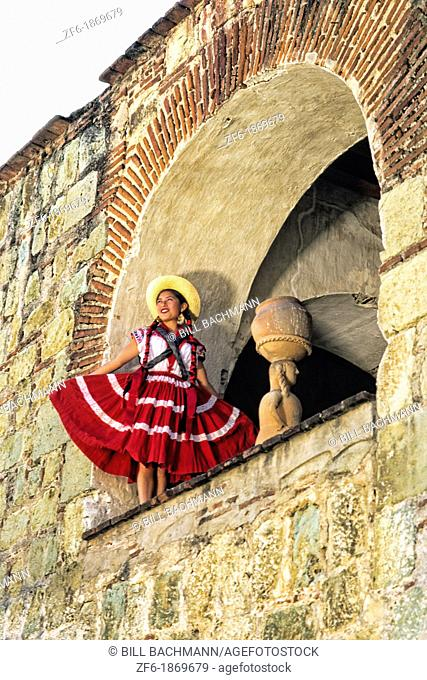 Colorful historical dancers in traditional dress in doorway from below in Oaxaca Mexico