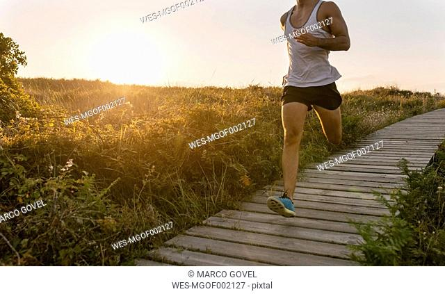 Spain, Aviles, athlete man running along a coastal path at sunset