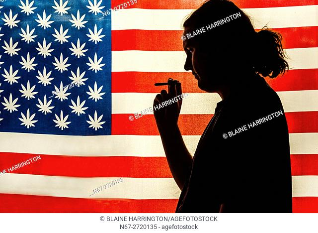 Man smoking a joint with American marijuana flag in background, Littleton, Colorado USA. Colorado was the first state to legalize the sale of marijuana for...