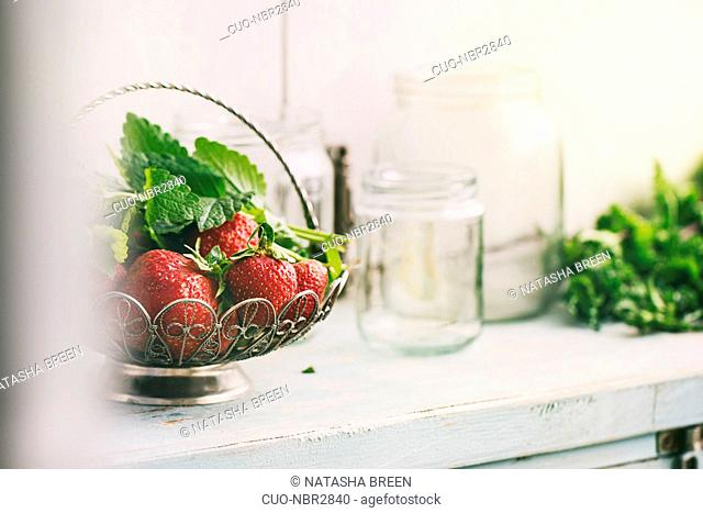 Fresh ripe garden strawberries and melissa herbs in vintage vase standing with empty glass jars for jam on blue white wooden kitchen table