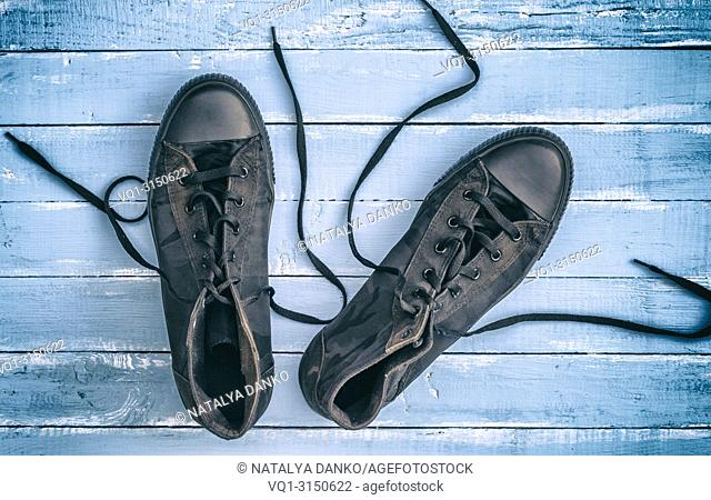 pair of black textile sneakers with loosened laces lie on a blue wooden background, top view