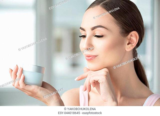 Perfect face. Profile of cheery young girl holding jar with cream in her palm in front of her face and looking at it. She is leaning her chin in other hand
