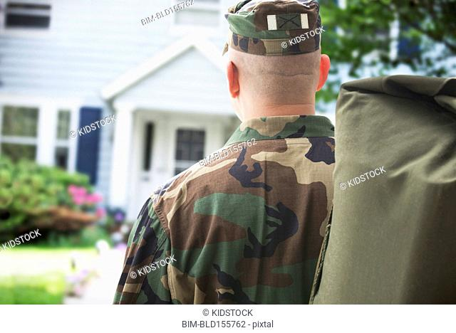 Caucasian returning soldier facing house