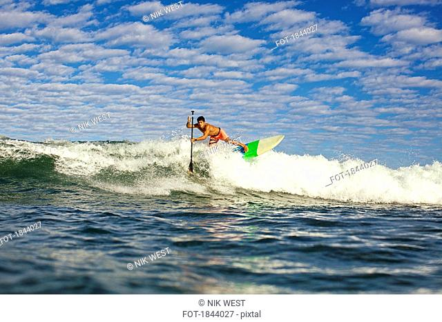Young man paddleboarding ocean wave