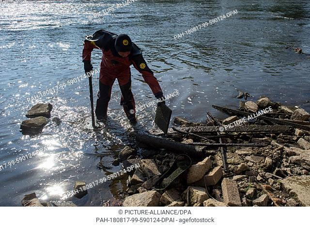 17 August 2018, Germany, Magdeburg: A diver of the Water and Shipping Authority removes scrap and bulky waste at the inlet of the gauge
