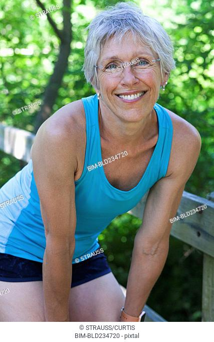 Caucasian woman resting wooden fence