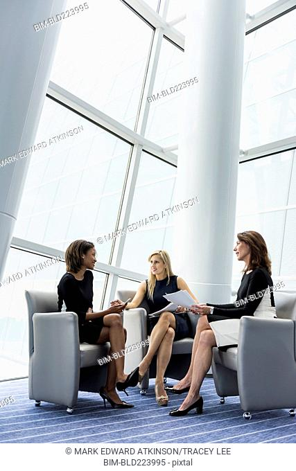 Businesswomen sitting in armchairs talking