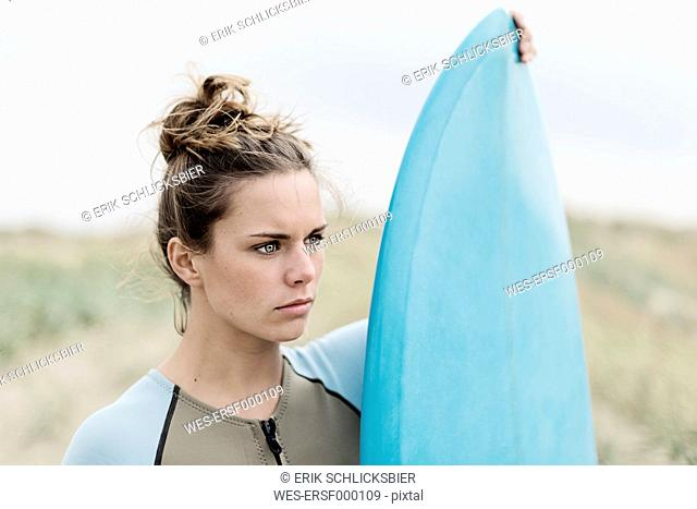 Portrait of young female surfer with surfboard